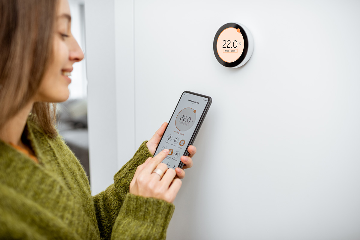 Woman setting up her smart thermostat on her smart phone